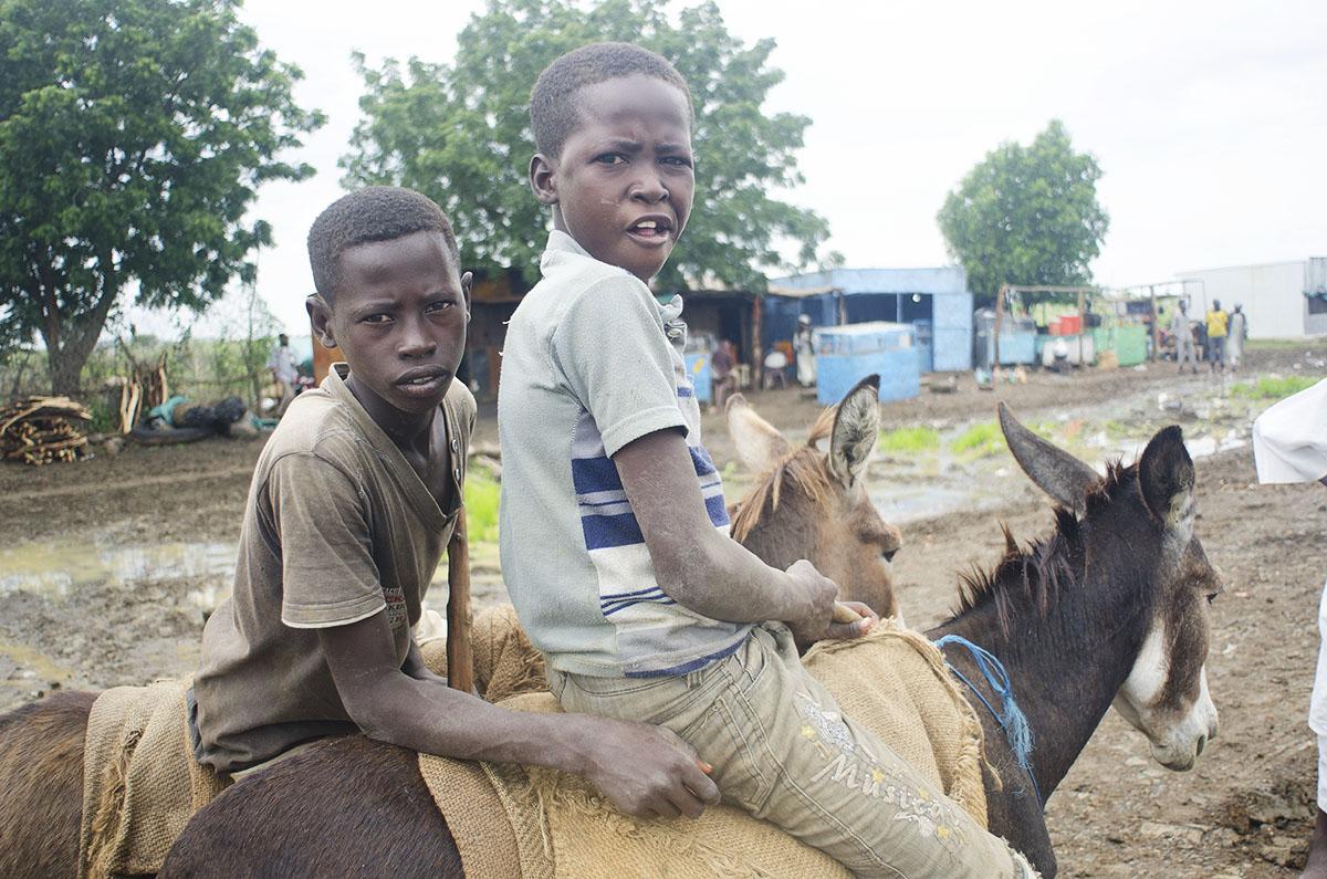 Niños montando en burro en Sudán.