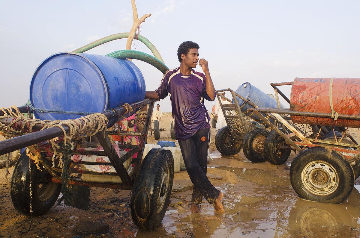 Chico sacando agua de un pozo en Sudán